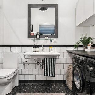 Mittelgroßes Skandinavisches Badezimmer En Suite mit Wandtoilette mit Spülkasten, weißen Fliesen, Porzellanfliesen, weißer Wandfarbe, Mosaik-Bodenfliesen, Wandwaschbecken, Laminat-Waschtisch und Wäscheaufbewahrung in Stockholm