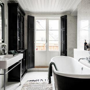 Idéer för att renovera ett minimalistiskt badrum, med ett fristående badkar, vit kakel, ett konsol handfat och vitt golv