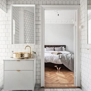 На фото: большая главная ванная комната в скандинавском стиле с плоскими фасадами, белыми фасадами, белой плиткой, керамической плиткой, белыми стенами, полом из известняка, настольной раковиной и мраморной столешницей с