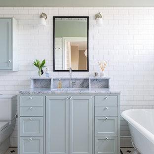 Inredning av ett klassiskt mellanstort badrum, med skåp i shakerstil, blå skåp, ett fristående badkar, grå väggar, ett undermonterad handfat, porslinskakel, klinkergolv i porslin och marmorbänkskiva