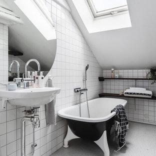 Minimalistisk inredning av ett badrum, med ett fristående badkar, en dusch/badkar-kombination, vit kakel, ett piedestal handfat, vitt golv och med dusch som är öppen
