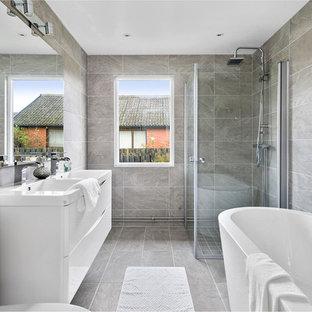 Inspiration för stora skandinaviska en-suite badrum, med släta luckor, vita skåp, en hörndusch, grå kakel, grått golv, dusch med gångjärnsdörr och ett integrerad handfat