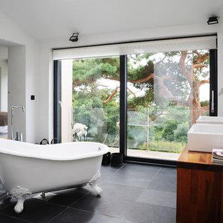 Inredning av ett modernt en-suite badrum, med skåp i mörkt trä, vita väggar och svart golv