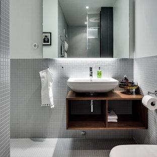 Foto på ett mellanstort nordiskt badrum med dusch, med öppna hyllor, skåp i mörkt trä, grå väggar, mosaikgolv, ett väggmonterat handfat, en toalettstol med hel cisternkåpa och träbänkskiva