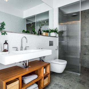 Idéer för mellanstora skandinaviska badrum med dusch, med öppna hyllor, skåp i mellenmörkt trä, en vägghängd toalettstol, grå kakel, mosaik, grått golv, en dusch i en alkov, vita väggar, ett konsol handfat och med dusch som är öppen