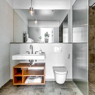 Modern inredning av ett badrum, med öppna hyllor, skåp i mellenmörkt trä, en hörndusch, en vägghängd toalettstol, träbänkskiva, vita väggar och brunt golv
