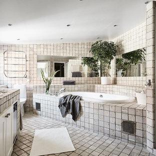 Foto på ett vintage badrum, med skåp i shakerstil, vita skåp, ett platsbyggt badkar, en toalettstol med hel cisternkåpa, beige kakel, beige väggar, ett nedsänkt handfat och beiget golv