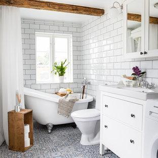 Exempel på ett mellanstort lantligt badrum med dusch, med möbel-liknande, vita skåp, ett badkar med tassar, en dusch/badkar-kombination, en toalettstol med hel cisternkåpa, vit kakel, vita väggar, cementgolv, tunnelbanekakel, ett konsol handfat, blått golv och dusch med duschdraperi