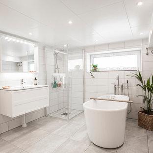 Inspiration för ett mellanstort funkis en-suite badrum, med vita skåp, ett fristående badkar, en hörndusch, grå kakel, vit kakel, vita väggar, ett konsol handfat, kalkstensgolv och dusch med gångjärnsdörr