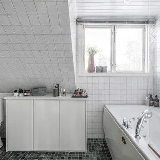 Bild på ett minimalistiskt vit vitt badrum, med vita skåp, ett hörnbadkar, en dusch/badkar-kombination, en toalettstol med hel cisternkåpa, vit kakel, vita väggar, grönt golv och med dusch som är öppen