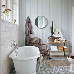 Inredning av ett lantligt mellanstort en-suite badrum, med öppna hyllor, ett fristående badkar, flerfärgad kakel, blå väggar, en toalettstol med hel cisternkåpa, porslinskakel, klinkergolv i keramik och träbänkskiva