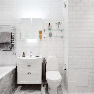 Inspiration för ett stort minimalistiskt badrum, med skåp i shakerstil, vita skåp, ett badkar i en alkov, en dusch/badkar-kombination, en toalettstol med separat cisternkåpa, vita väggar, marmorgolv, ett konsol handfat och tunnelbanekakel