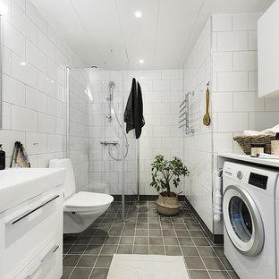 Inspiration för ett skandinaviskt vit vitt badrum med dusch, med släta luckor, vita skåp, en hörndusch, en toalettstol med separat cisternkåpa, vit kakel, ett integrerad handfat, grått golv och dusch med gångjärnsdörr