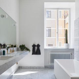 Exempel på ett skandinaviskt grå grått en-suite badrum, med ett fristående badkar, grå kakel, vita väggar, ett väggmonterat handfat och grått golv