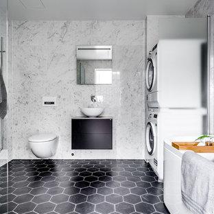 Idéer för ett stort modernt badrum, med möbel-liknande, svarta skåp, ett fristående badkar, en vägghängd toalettstol, vit kakel, marmorkakel, ett fristående handfat och svart golv