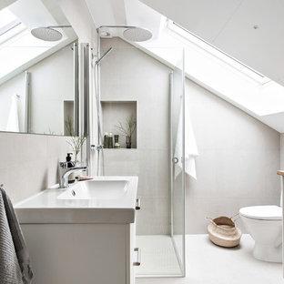 Foto på ett mellanstort skandinaviskt badrum med dusch, med vita skåp, en hörndusch, träbänkskiva, vitt golv, dusch med gångjärnsdörr, släta luckor, grå kakel och ett konsol handfat