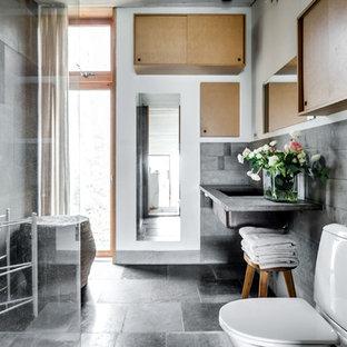 Modelo de cuarto de baño con ducha, industrial, grande, con armarios con paneles lisos, puertas de armario de madera clara, sanitario de una pieza, paredes grises, suelo de cemento, lavabo encastrado y encimera de cemento