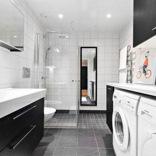 Inredning av ett modernt vit vitt badrum med dusch, med svarta skåp, en hörndusch, en vägghängd toalettstol, vit kakel, vita väggar, klinkergolv i keramik, grått golv och dusch med gångjärnsdörr