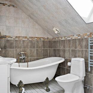 Inredning av ett lantligt litet grå grått badrum med dusch, med vita skåp, ett badkar med tassar, en dusch/badkar-kombination, en toalettstol med hel cisternkåpa, beige kakel, brun kakel, vitt golv, flerfärgade väggar, ett integrerad handfat och med dusch som är öppen