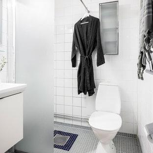 Idéer för att renovera ett minimalistiskt vit vitt badrum med dusch, med släta luckor, vita skåp, en hörndusch, en toalettstol med hel cisternkåpa, vit kakel, vita väggar, mosaikgolv, ett konsol handfat, grått golv och med dusch som är öppen