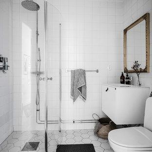 Idéer för ett minimalistiskt badrum med dusch, med släta luckor, vita skåp, en hörndusch, en toalettstol med separat cisternkåpa, vit kakel, vita väggar, grått golv och dusch med gångjärnsdörr