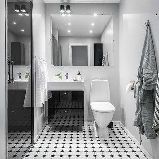 Inspiration för mellanstora minimalistiska badrum med dusch, med släta luckor, svarta skåp, en toalettstol med hel cisternkåpa, vita väggar, flerfärgat golv, en dusch i en alkov, cementgolv, ett konsol handfat och dusch med gångjärnsdörr