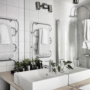 Bild på ett skandinaviskt badrum, med vit kakel, vita väggar, ett fristående handfat och träbänkskiva