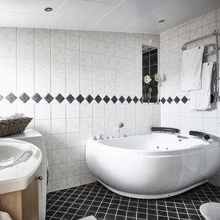 Foto på ett minimalistiskt badrum, med ett hörnbadkar, en hörndusch, vit kakel, vita väggar, ett integrerad handfat och svart golv