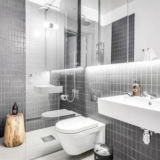 Idéer för ett mellanstort modernt badrum, med en kantlös dusch, en vägghängd toalettstol, grå kakel, grå väggar, ett väggmonterat handfat, vitt golv och med dusch som är öppen