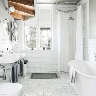 Exempel på ett skandinaviskt badrum, med ett fristående badkar, en toalettstol med separat cisternkåpa, vit kakel, tunnelbanekakel, ett konsol handfat, vitt golv och dusch med duschdraperi