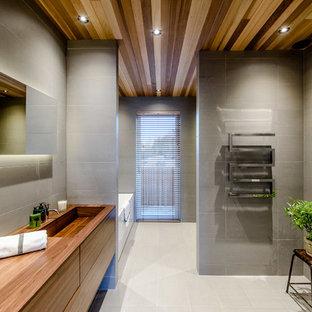 Idéer för ett mellanstort modernt brun badrum, med släta luckor, skåp i mellenmörkt trä, grå kakel, grå väggar, ett integrerad handfat och träbänkskiva