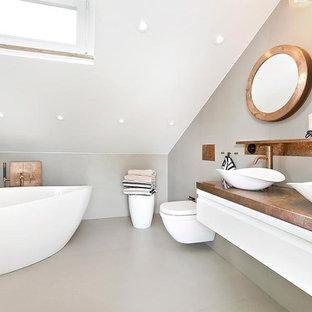 Bild på ett stort funkis badrum, med ett fristående badkar, en vägghängd toalettstol, vita väggar, betonggolv och ett fristående handfat