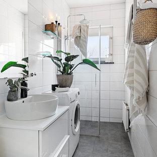 Nordisk inredning av ett vit vitt badrum, med släta luckor, vita skåp, en dusch i en alkov, vit kakel, ett fristående handfat och grått golv