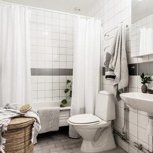 Foto di una stanza da bagno con doccia nordica con nessun'anta, vasca freestanding, vasca/doccia, WC a due pezzi, piastrelle grigie, piastrelle bianche, piastrelle in gres porcellanato, pareti bianche, pavimento in mattoni, lavabo sospeso, pavimento grigio e doccia con tenda