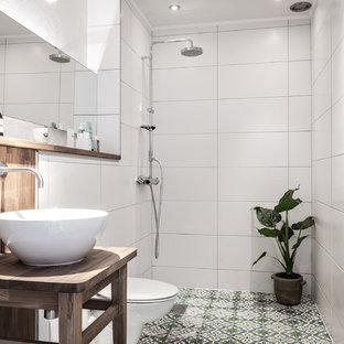 Ispirazione per una stanza da bagno con doccia nordica di medie dimensioni con ante di vetro, ante in legno bruno, doccia aperta, piastrelle bianche, pavimento in cementine, lavabo a bacinella e pavimento multicolore