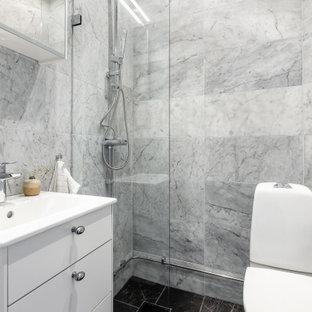 Inspiration för mellanstora moderna vitt badrum med dusch, med släta luckor, vita skåp, en hörndusch, en toalettstol med hel cisternkåpa, grå kakel, ett integrerad handfat, svart golv och med dusch som är öppen