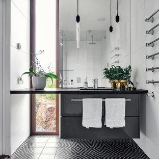 Idéer för ett mellanstort modernt svart badrum, med vita väggar, ett integrerad handfat, svart golv, släta luckor, grå skåp, vit kakel och mosaikgolv