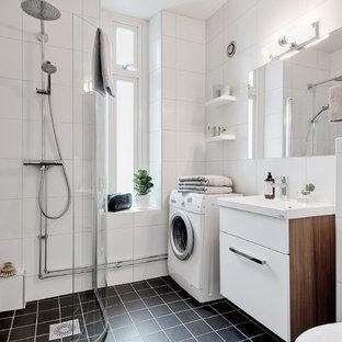 Inspiration för nordiska badrum med dusch, med släta luckor, vita skåp, en hörndusch, vit kakel, ett konsol handfat och svart golv