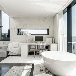 Inspiration för ett stort funkis grå grått en-suite badrum, med ett fristående badkar, grå väggar och svart golv