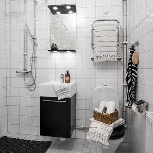 Bild på ett litet nordiskt vit vitt badrum med dusch, med släta luckor, svarta skåp, en hörndusch, en toalettstol med hel cisternkåpa, vit kakel, ett integrerad handfat, vitt golv och med dusch som är öppen