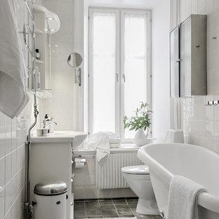 Inredning av ett nordiskt badrum, med vit kakel, vita skåp, ett badkar med tassar, vita väggar, ett konsol handfat och grått golv