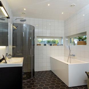 Modern inredning av ett mellanstort vit vitt badrum med dusch, med släta luckor, svarta skåp, ett hörnbadkar, en hörndusch, vit kakel, porslinskakel, klinkergolv i porslin, ett integrerad handfat, svart golv och dusch med gångjärnsdörr