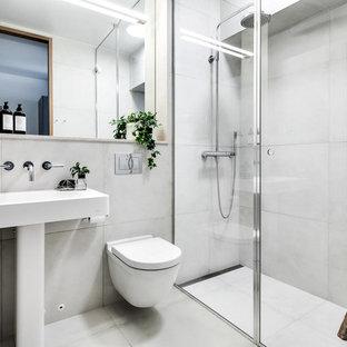 Exempel på ett mellanstort skandinaviskt badrum med dusch, med en hörndusch, vit kakel, vita väggar, en vägghängd toalettstol, cementkakel, ett piedestal handfat, grått golv och med dusch som är öppen