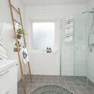 Foto de cuarto de baño con ducha, nórdico, grande, con armarios con paneles lisos, puertas de armario blancas, ducha esquinera, baldosas y/o azulejos grises, baldosas y/o azulejos blancos, paredes blancas, lavabo integrado, baldosas y/o azulejos de cerámica y ducha con puerta con bisagras