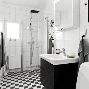 Inredning av ett skandinaviskt badrum med dusch, med släta luckor, svarta skåp, en hörndusch, vit kakel, vita väggar, ett konsol handfat, dusch med gångjärnsdörr och flerfärgat golv
