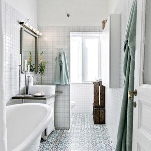 Nordisk inredning av ett mellanstort grå grått badrum med dusch, med ett badkar med tassar, en dusch/badkar-kombination, vit kakel, dusch med duschdraperi, släta luckor, vita skåp, vita väggar, ett konsol handfat och flerfärgat golv