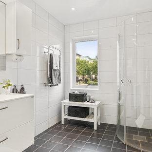 Idéer för minimalistiska badrum med dusch, med släta luckor, vita skåp, en hörndusch, vit kakel, ett konsol handfat, svart golv och dusch med gångjärnsdörr
