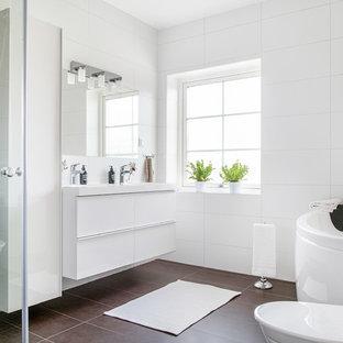 Inredning av ett modernt mellanstort en-suite badrum, med släta luckor, vita skåp, ett fristående badkar, svart och vit kakel, vita väggar och ett konsol handfat