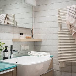 Minimalistisk inredning av ett vit vitt badrum, med släta luckor, skåp i ljust trä, vit kakel, ett nedsänkt handfat och bänkskiva i glas