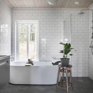 Idéer för att renovera ett minimalistiskt vit vitt en-suite badrum, med släta luckor, grå skåp, ett fristående badkar, en kantlös dusch, vit kakel, tunnelbanekakel, ett nedsänkt handfat, grått golv och dusch med gångjärnsdörr